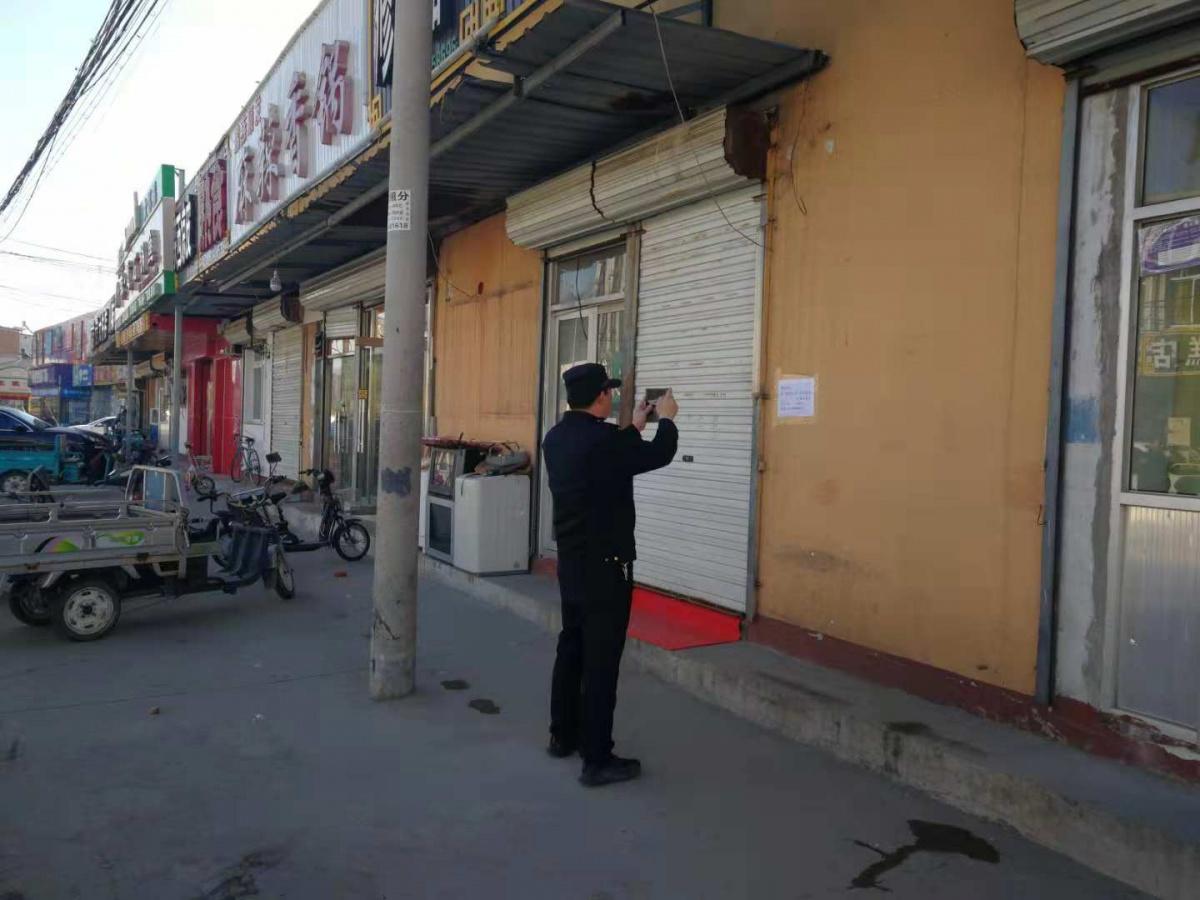十里堡镇执法队对张贴在墙上的小广告进行拍照取证.jpg