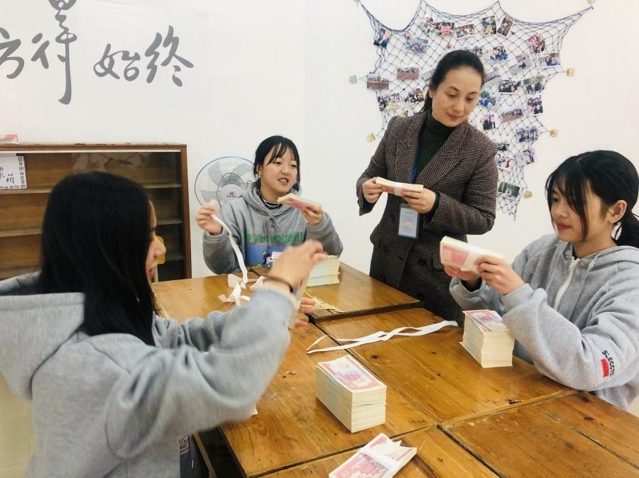 陈艳教师正在指导参赛选手进行扎钞训练.jpg