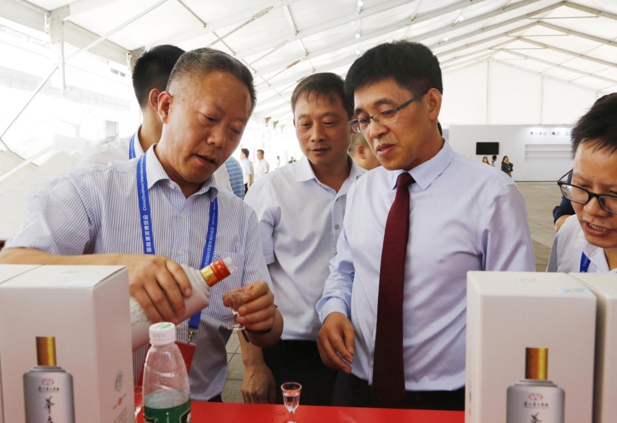 1王开馥(左)向李静仁(右)介绍茅台不老酒.JPG